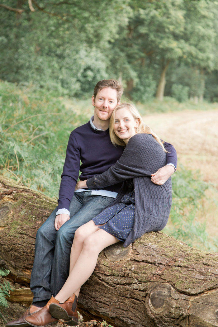 Woodland Engagement Shoot natural couple cuddling on fallen tree