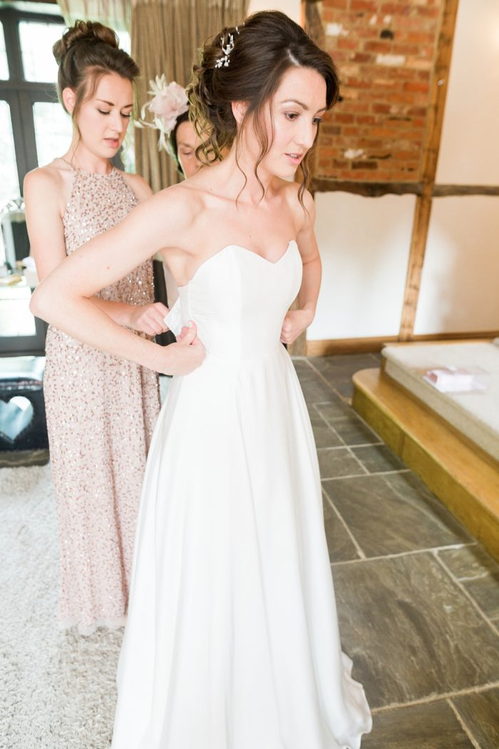 Rivervale Barn wedding photography bride getting into dress