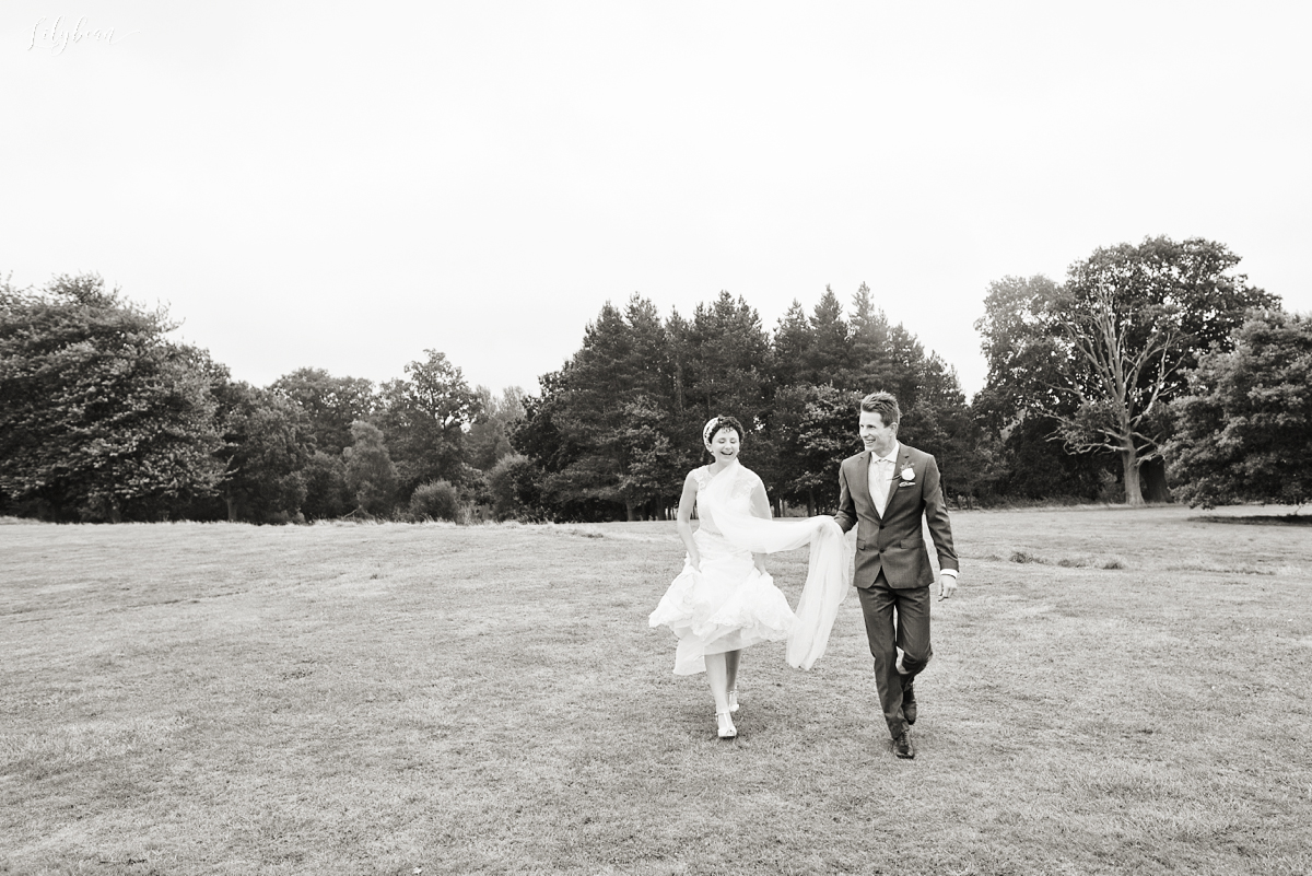Fun walking shot of Bride & Groom in the rain
