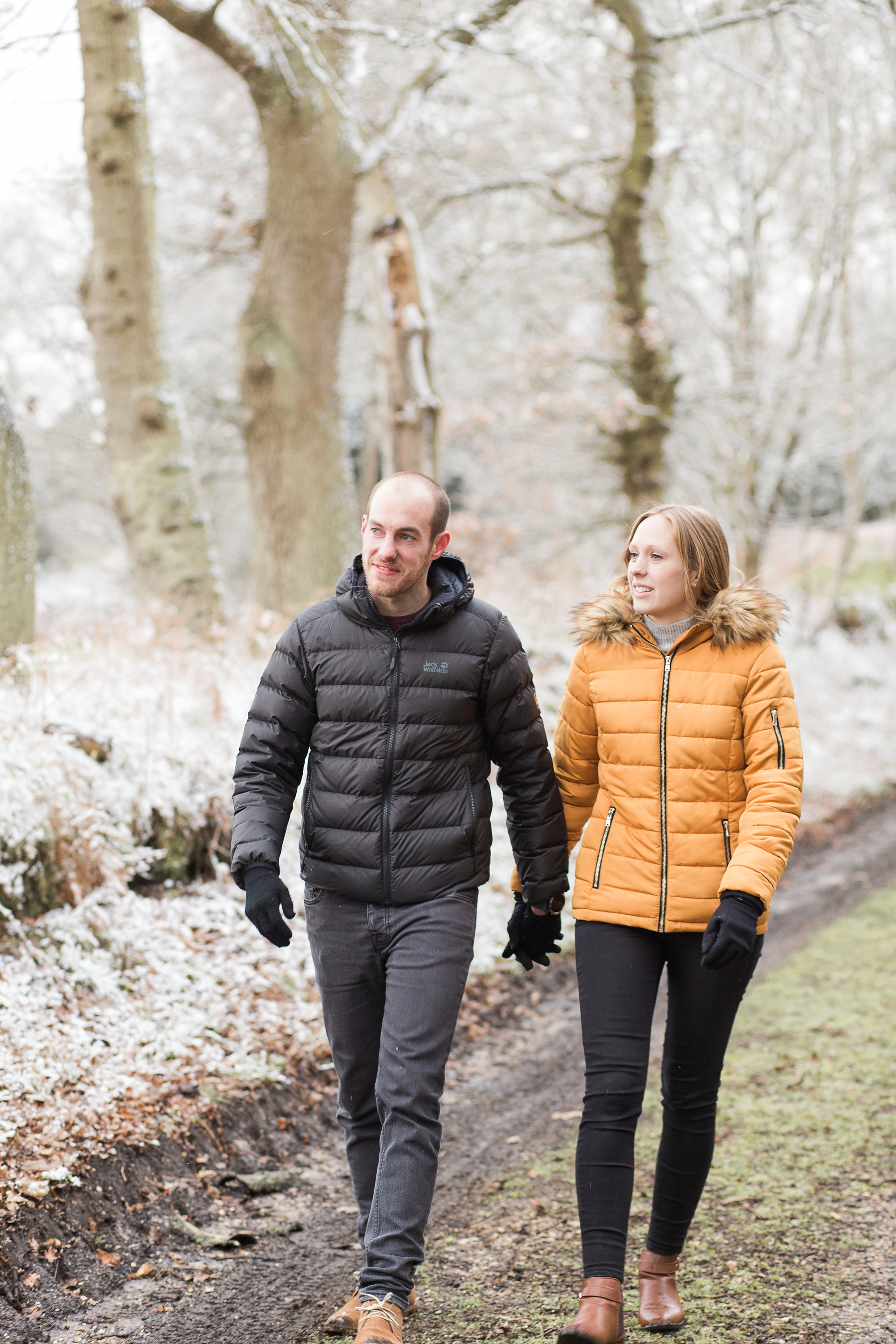 Woodland Engagement Shoot in snow couple walking country lane