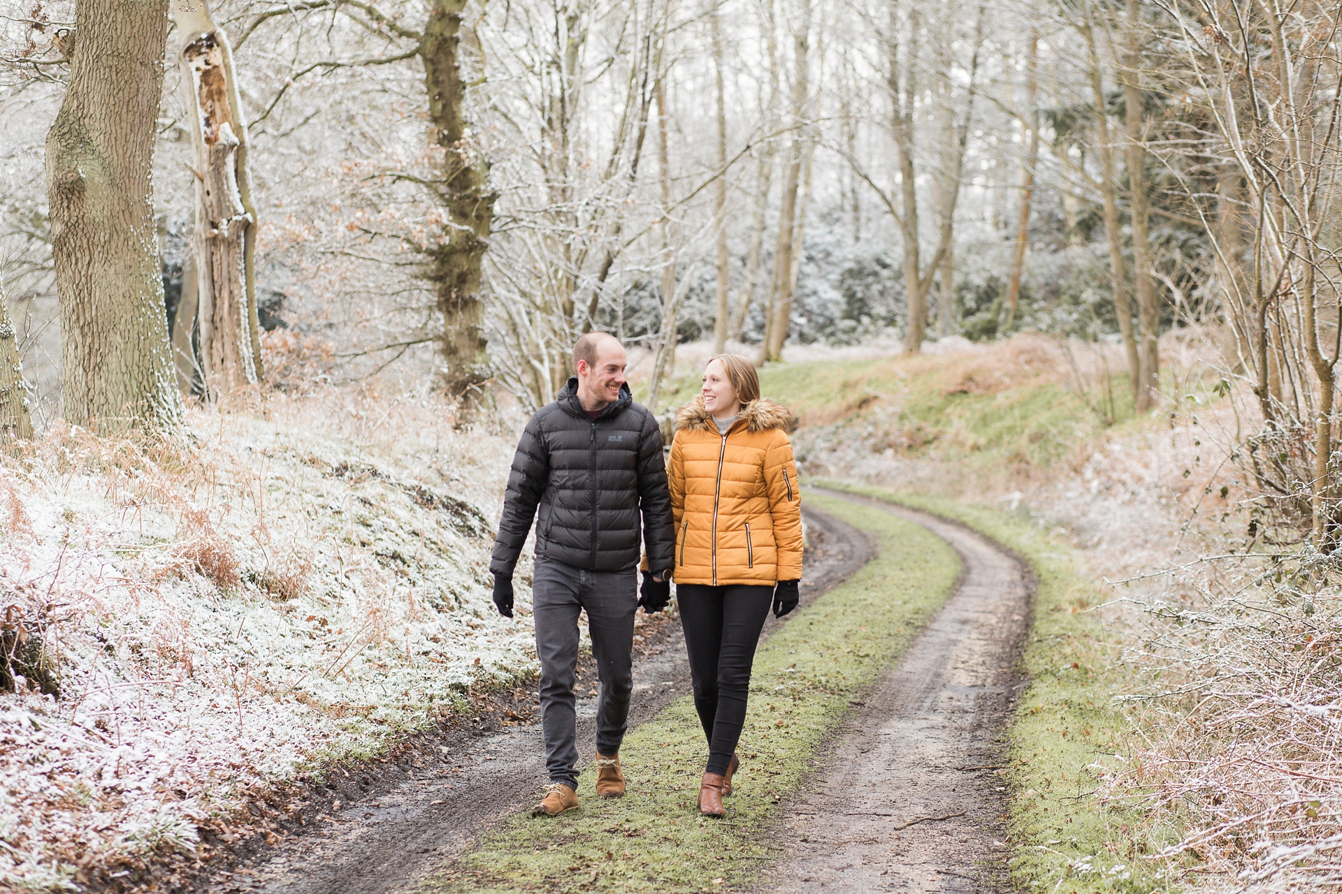 Woodland Engagement Shoot in snow couple walking in woodland