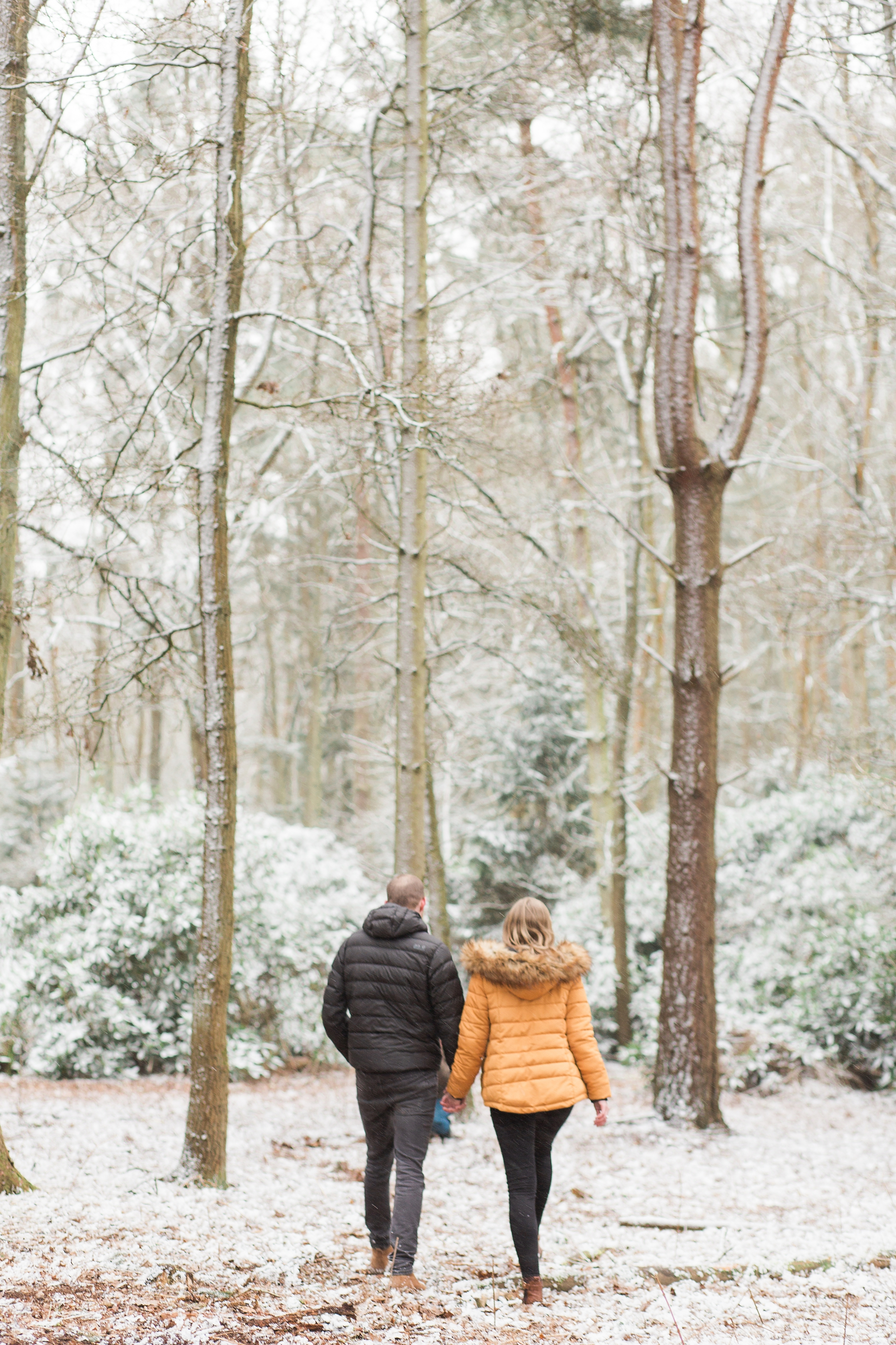 Woodland Engagement Shoot in snow couple walking away