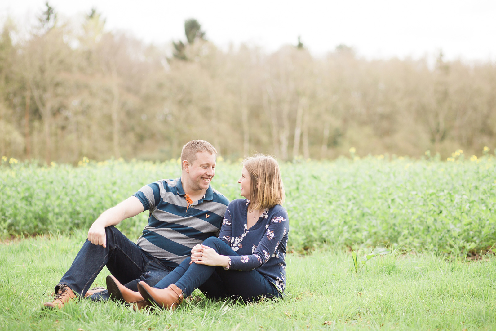 Dreamy woodland engagement shoot couple sat on grass