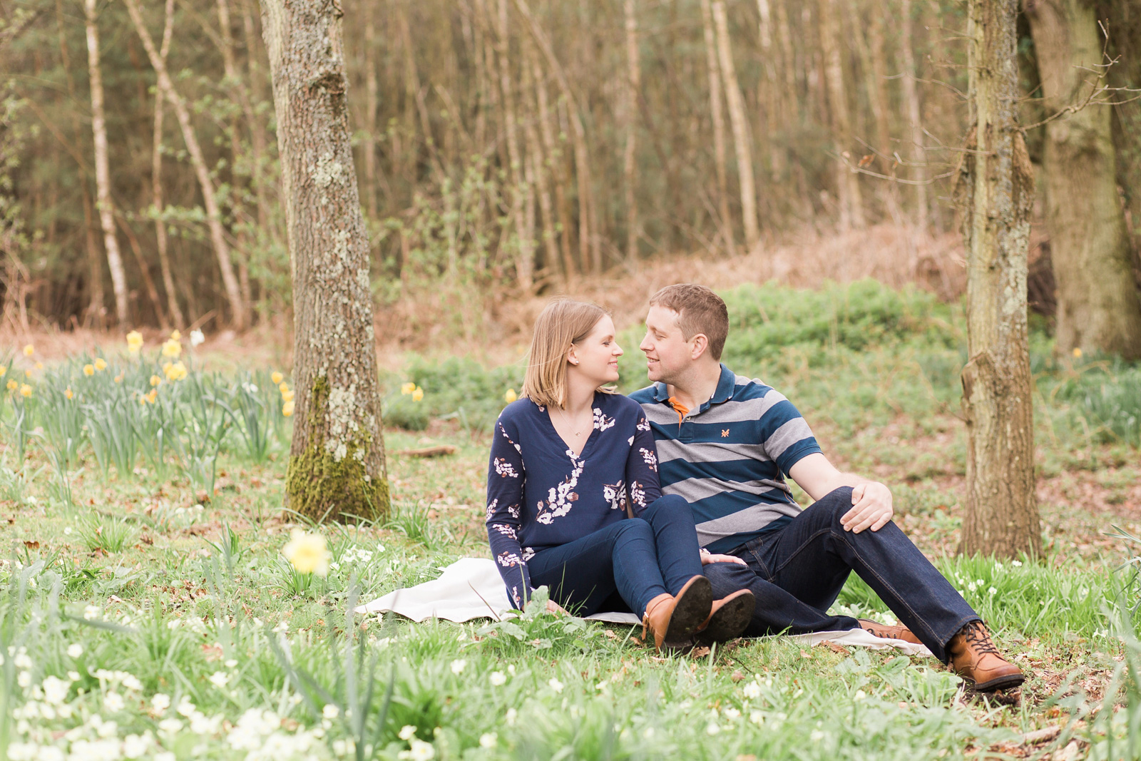 Dreamy woodland engagement shoot couple sat among spring flowers